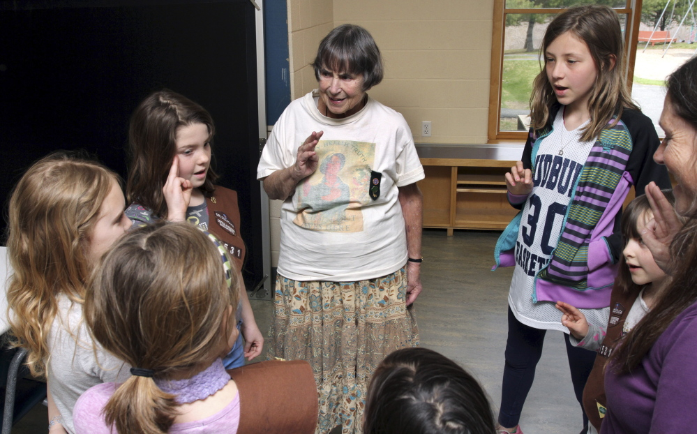 Molly Robinson, center, recites the Girl Scout Promise during a meeting with her troop in Greenfield, Mass. Robinson still projects a vitality and sense of leadership that is not diminished by her use of a walker or wheelchair.