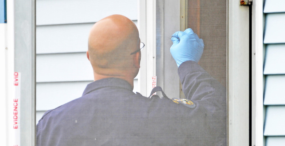 An investigator with the Maine State Police Major Crimes Unit examines a door at the back entrance to the residence of Aurele Fecteau, 92, who was found dead in his home on Brooklyn Street in Waterville on Friday.