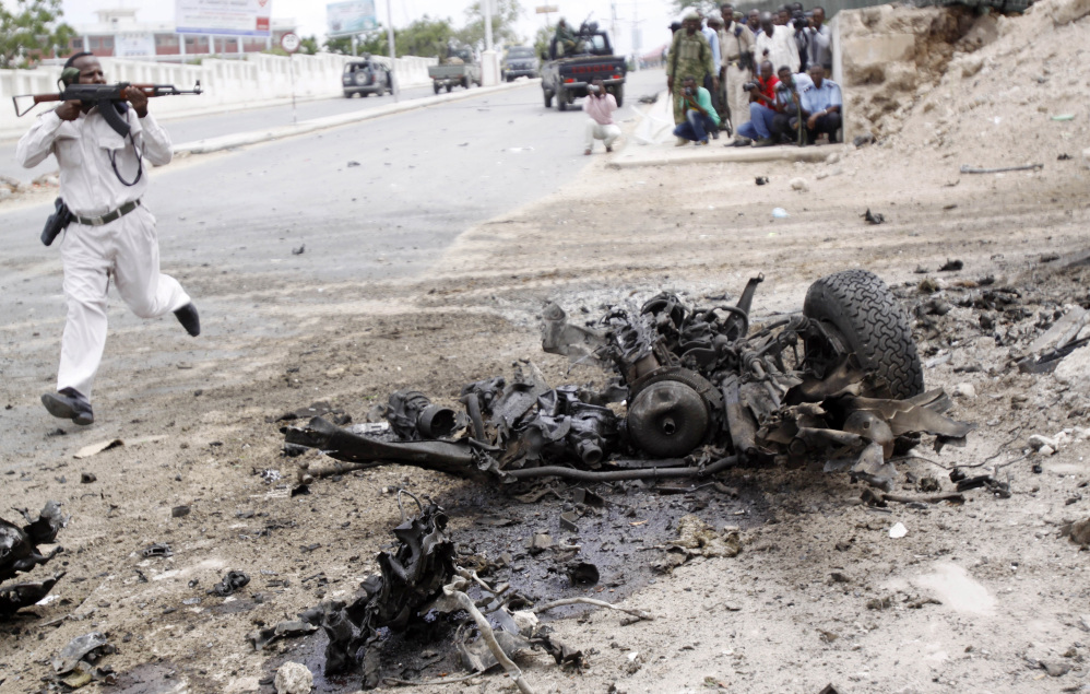 A Somali soldier runs past the wreckage from a car bomb during an attack on the parliament building on Saturday in Mogadishu, Somalia. Among those reported killed are six attackers and a soldier who tried to stop a suicide bomber from entering the building.