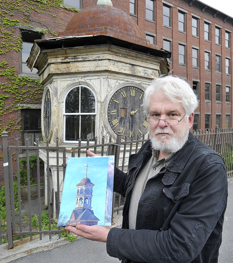 Historian George Collord of Portland shows an image of the original condition of the clock tower in this May 2014 photo.