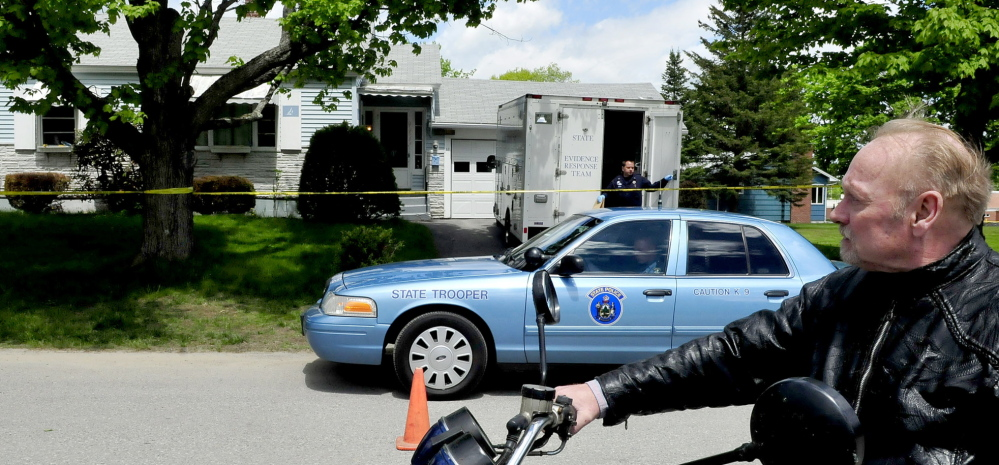 Paul Fecteau watches as a Maine State Police detective exits a Maine State Police Major Crime Unit vehicle outside the cordoned-off home of his father, Aurele Fecteau, in Waterville on Sunday. Aurele Fecteau was found dead by his elder brother Ernest on Friday, according to Paul Fecteau. The death was ruled a homicide on Sunday.
