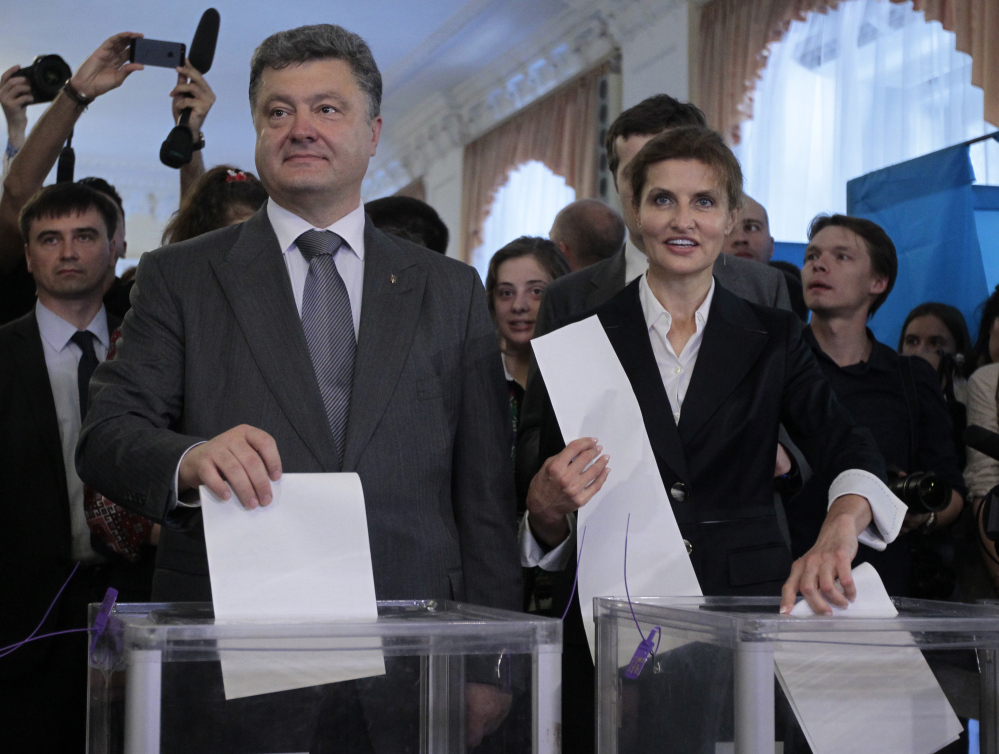 Ukrainian presidential candidate Petro Poroshenko, left, and his wife, Maria, right, cast their ballots at a polling station in Kiev, Ukraine, on Sunday.
