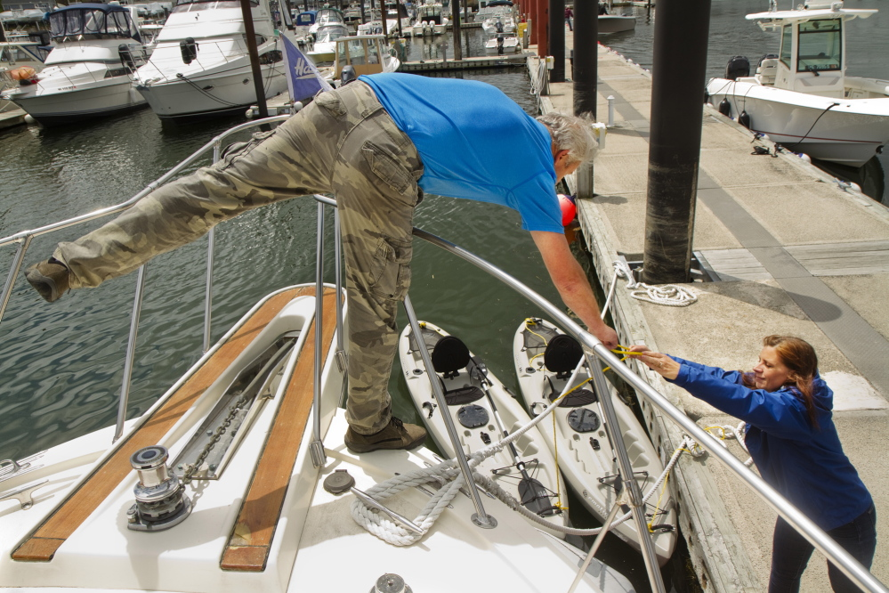 Kim Galanif of South Portland hands the line of a kayak to her husband, Ken, on the bow of their boat at Spring Point Marina in South Portland on Sunday. The couple was loading the smaller boats onto the larger vessel before going out for a cruise, then a paddle in Casco Bay.