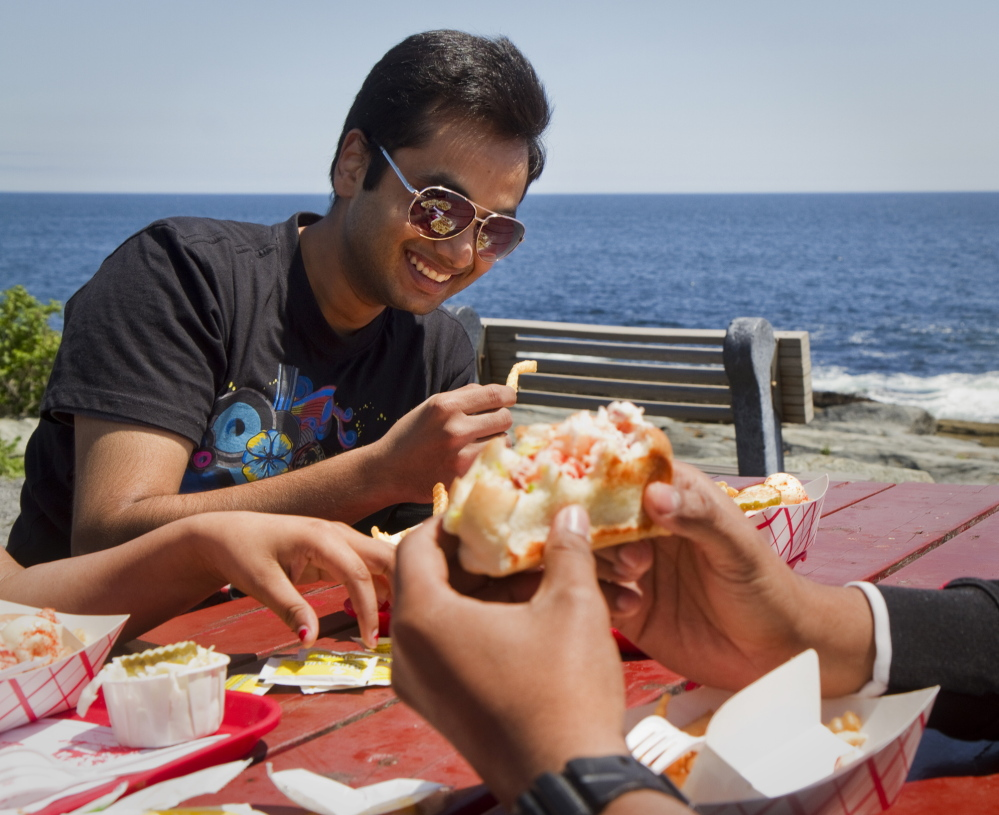 Yogesh Kauntia enjoys good friends and good food at the Lobster Shack at Two Lights in Cape Elizabeth as part of his Memorial Day weekend in Maine on Sunday.