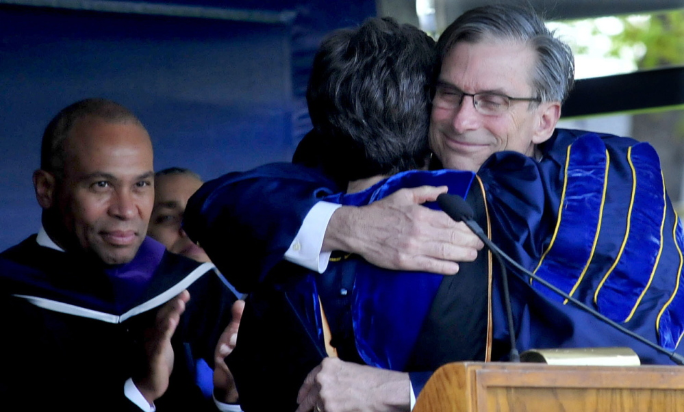 Retiring Colby College President William D. Adams hugs Dean of Faculty Lori Kletcher after receiving an honorary Doctor of Letters degree during his final commencement Sunday. At left is Massachusetts Gov. Deval Patrick.