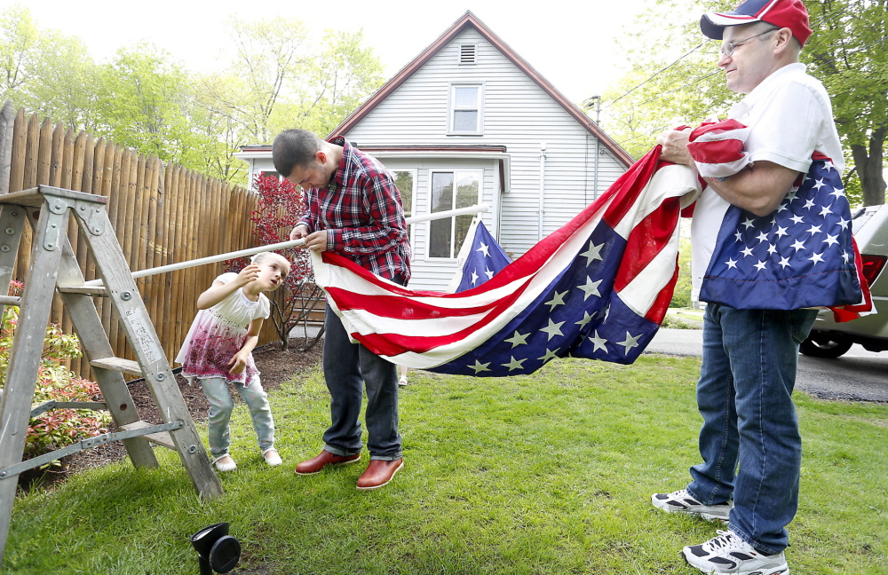 Gary Aldrich, right, his son Phil and granddaughter Jaelynn, 6, hang an American flag at Aldrich's home in Sanford on Monday. The flag draped the casket during the funeral of Aldrich's grandfather, a World War I veteran, in 1966 in Old Town.