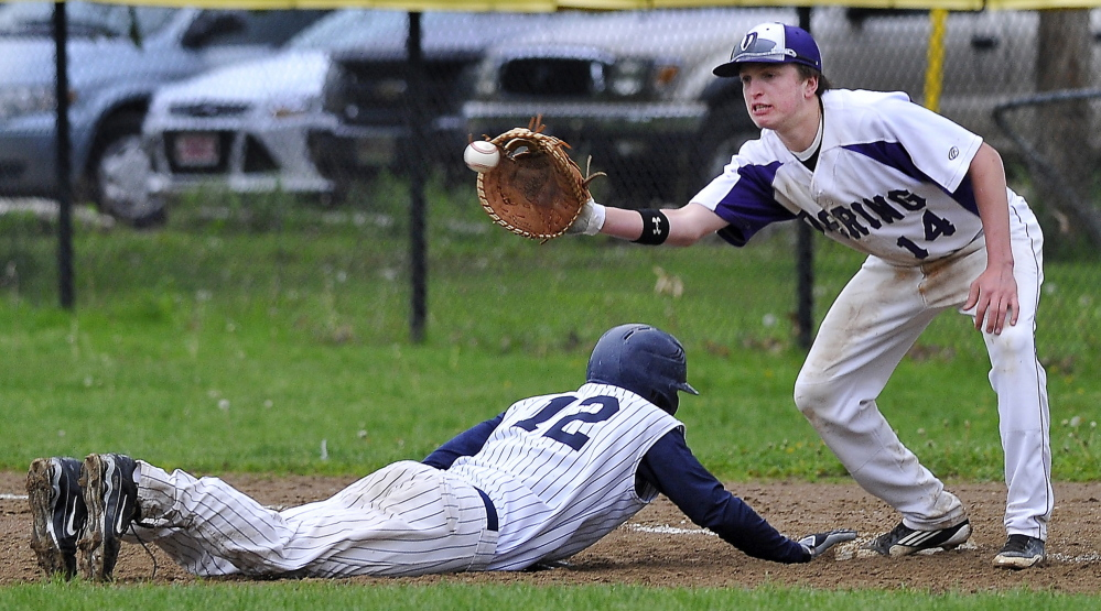 Justin Zukowski of Portland slides safely back to first base as Ben Peterson of Deering takes the pickoff throw Tuesday during their SMAA baseball game at Deering Oaks in Portland. Zukowski had two hits for the Bulldogs, who came away with a 10-1 victory. High school roundup, D5.