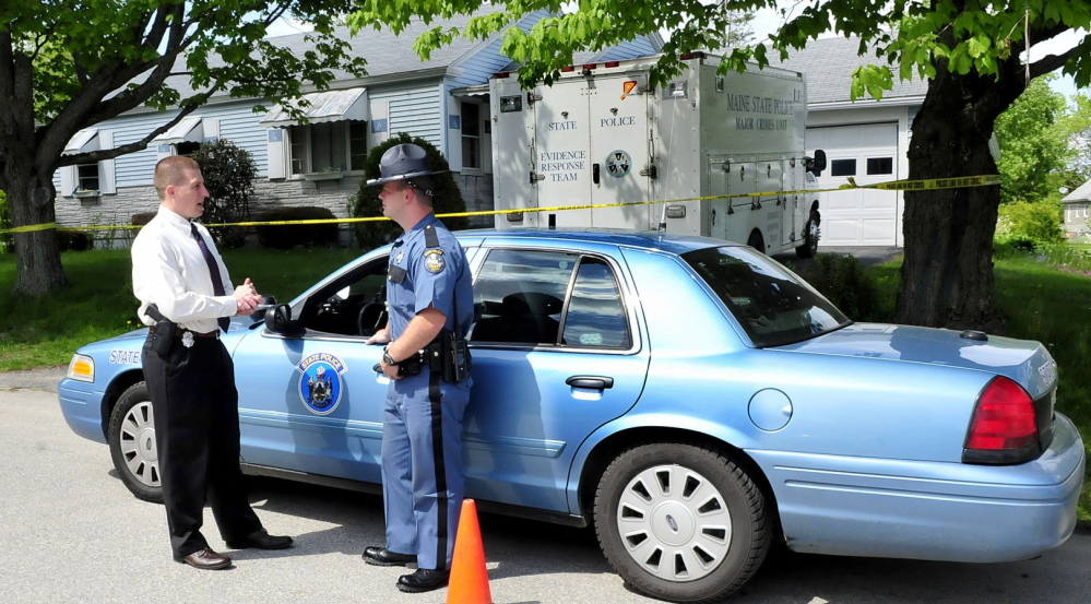 Maine State Police Sgt. Jeffrey Love, left, and trooper Randy Hall confer on Monday as investigators searched for evidence inside the Brooklyn Avenue home of Aurele Fecteau in Waterville.