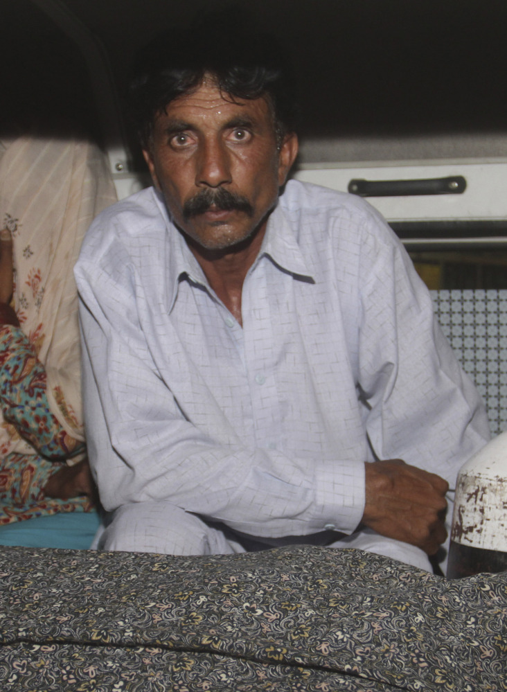 Mohammad Iqbal sits in an ambulance Tuesday with the body of his wife, stoning victim Farzana Parveen, 25.