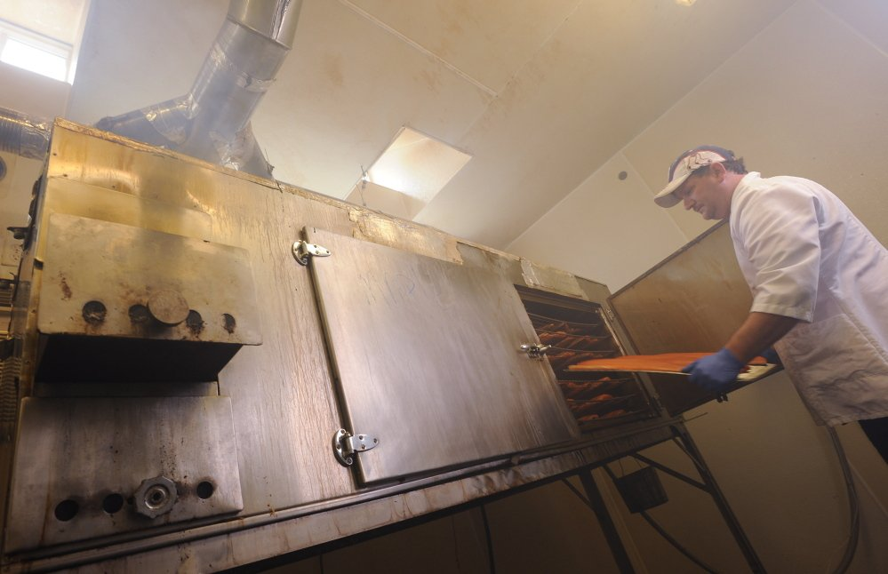 Jamie Young removes smoked salmon from one of three kilns at Sullivan Harbor Farm smokehouse in Hancock. Kevin Bennett photos