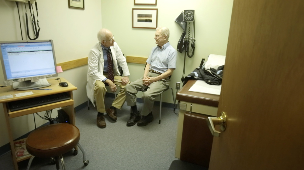 "Dr. William Medd talks with patient Frank Floster at Medd's primary care practice in Norway. Medd, 71, recently recovered from heart surgery and worries about who take his place when he retires. ""You don't want to feel like you're abandoning your patients,"" he said."