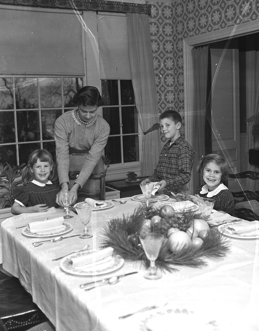 Preparing for a large holiday dinner group are the family of Dr. Howard R. Ives of Bowdoin St., left to right: Cindy, 4, Mrs. Ives, Rollin, 8, and Sally, 7.