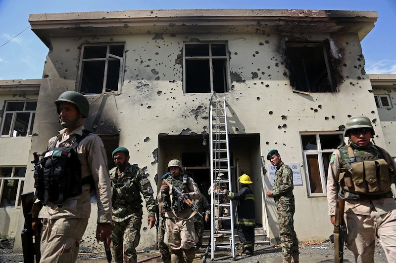 Afghan security personnel surround the area after Taliban fighters stormed a government building in Jalalabad, east of Kabul, Afghanistan, Monday, May 12, 2014. Taliban fighters stormed a government building in eastern Afghanistan killing police guards on Monday, the most serious in a wave of attacks marking the start of the insurgents' annual spring offensive. In the Taliban heartland in the south, an attack on a police checkpoint in Helmand province killed many policemen.