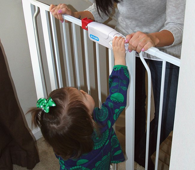In this photo provided by Nationwide Children's Hospital, Jessica Fannon talks to her daughter, Ella, through a mounted baby gate in her home in Grove City, Ohio. When she was just 9 months old Ella pushed through a tension-mounted gate and fell down 14 steps.