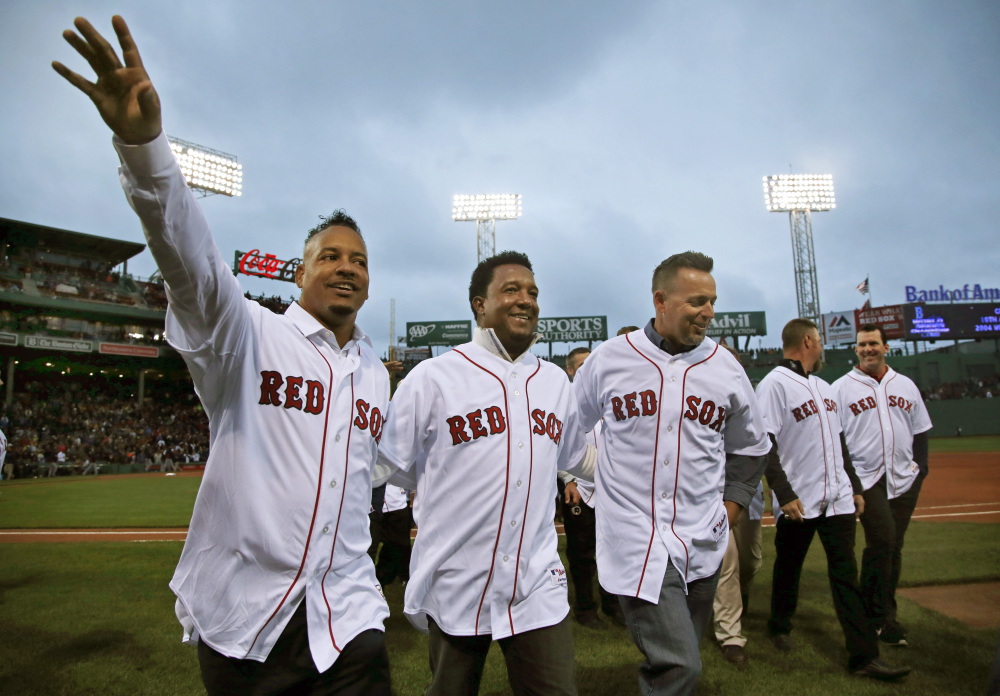 Former Boston Red Sox players, from left, Manny Ramirez, Pedro Martinez and Kevin Millar leave the field after they celebrated with teammates from 2004 at Fenway Park prior to a baseball game against the Atlanta Braves in Boston, Wednesday, May 28, 2014. The Red Sox honored the 10th anniversary of the 2004 World Series team before the game. The Associated Press/Elise Amendola