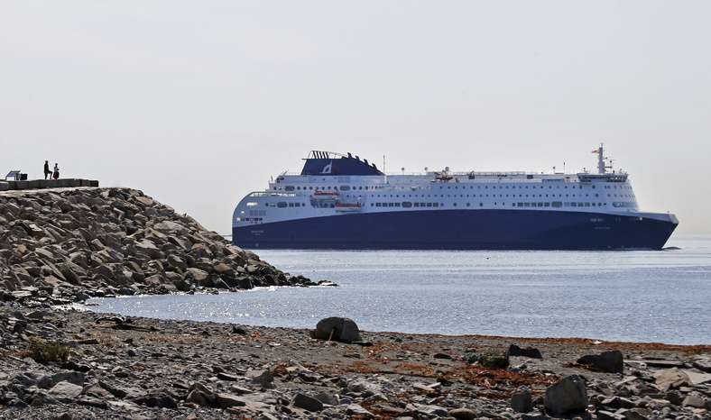 Two people watch the Nova Star cruise ferry make its way into Boston Harbor on Monday. The ferry will begin daily round trips between Portland and Nova Scotia on Thursday.