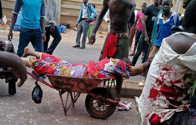 An injured woman is carried after bombs exploded at a bus terminal and market in Jos, Nigeria.