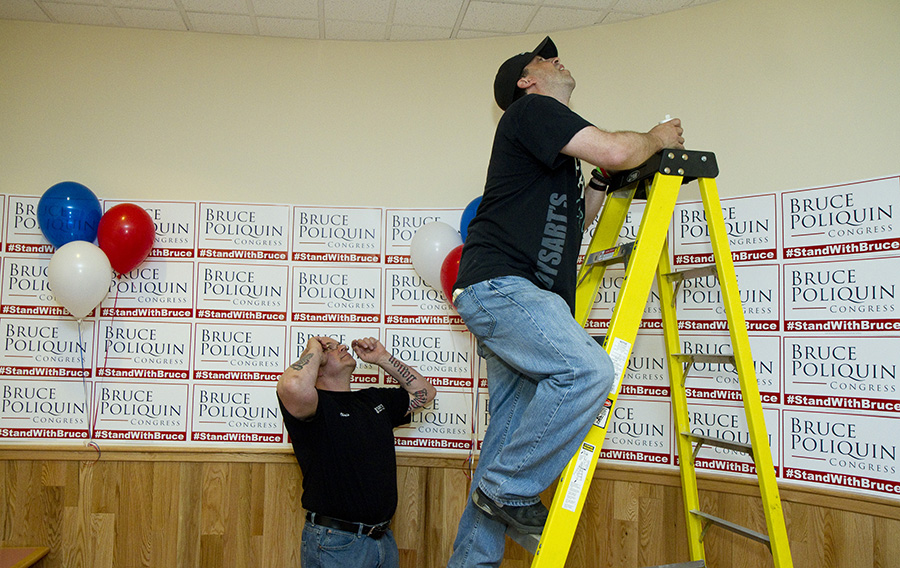 Dysarts Broadway staff member Chris Gaudet watches as John Mason climbs a ladder to replace a light bulb before Bruce Poliquin's Primary night gathering. Carl D. Walsh/Staff Photographer