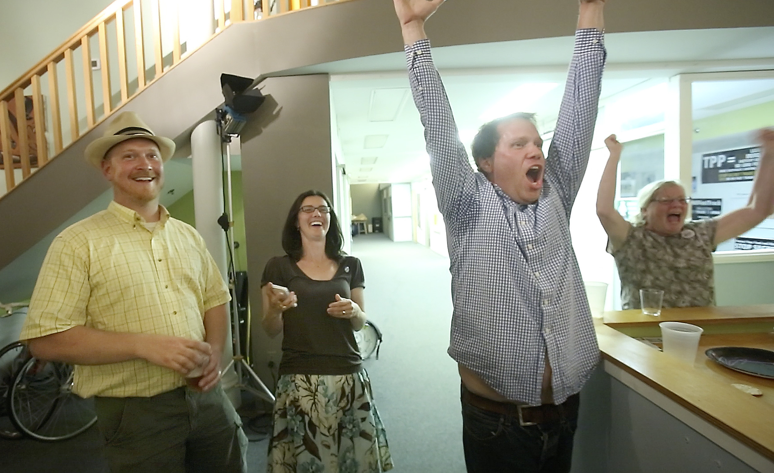 Chris Moore, right, a volunteer with the Yes on 1 campaign, his wife Bree LaCasse, center and councilor David Marshall celebrate victory in Portland for the campaign that sought to save Congress Square Plaza from being sold for development.