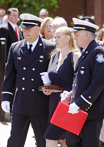 Marcia Kucsma is escorted out of the Cathedral of the Immaculate Conception following the funeral service for her husband, Portland Fire Capt. Michael Kucsma, in Portland Saturday. Jill Brady/Staff Photographer