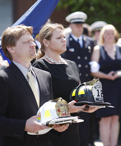 Sarah and Christopher Kucsma, the sister and brother of Portland Fire Capt. Michael Kucsma, carry his Portland and Gorham fire helmets following his funeral service at the Cathedral of the Immaculate Conception in Portland Saturday. Jill Brady/Staff Photographer