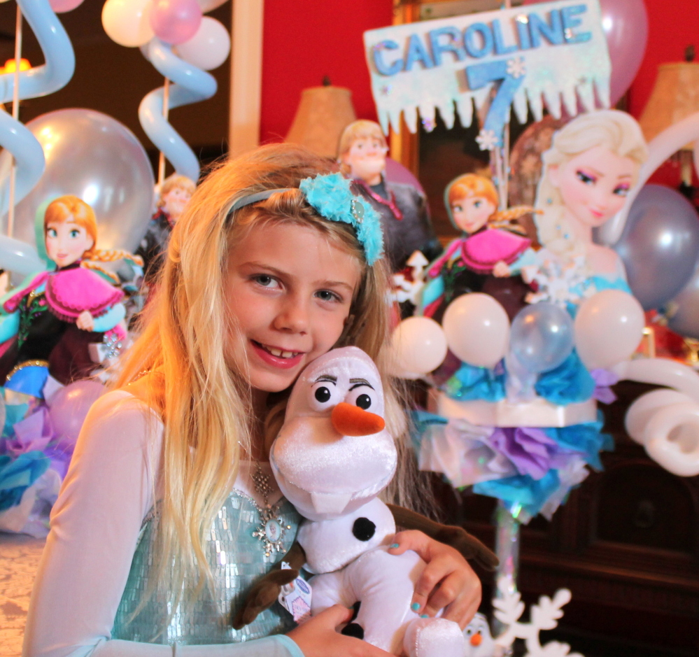 "In a photo provided by her mother, Caroline Calder holds a stuffed snowman named Olaf, a character in ""Frozen,"" at her birthday party in May, and wears a hard-to-find dress based on princess attire in the film. The Associated Press"