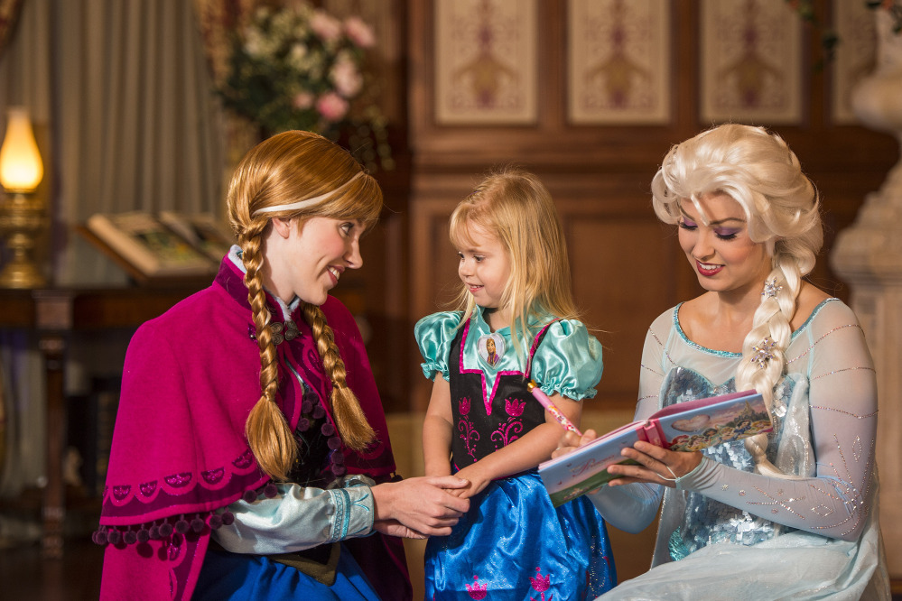 "Disney characters playing princesses from the animated movie ""Frozen,"" Anna, left, and her sister Elsa, right, talk with a young fan at Walt Disney World Resort in Lake Buena Vista, Fla. Wait times to meet the sisters stretches for hours and reservations are snapped up quickly. The Associated Press"