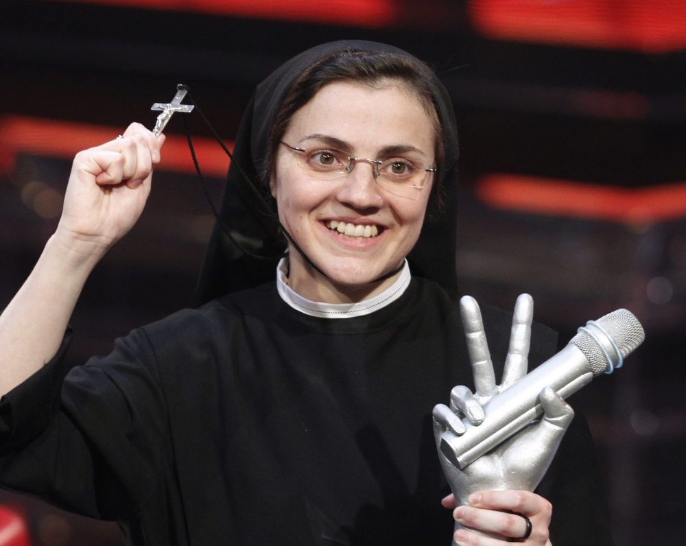 "Sister Cristina Scuccia poses with the trophy and holding a cross after winning the final of the Italian version of the TV talent show ""The Voice"" in Milan, Italy, on Friday. The Associated Press"