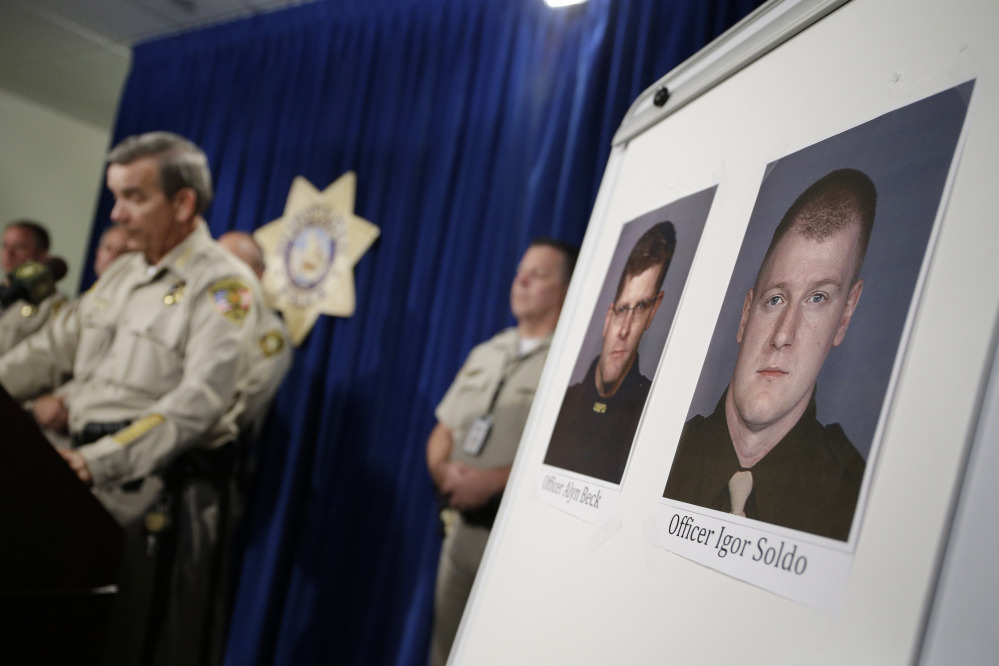 Sheriff Doug Gillespie, left, speaks at a news conference on the shooting of two Las Vegas Metropolitan Police Department officers Sunday in Las Vegas. The two officer killed were Alyn Beck and Igor Soldo. The Associated Press