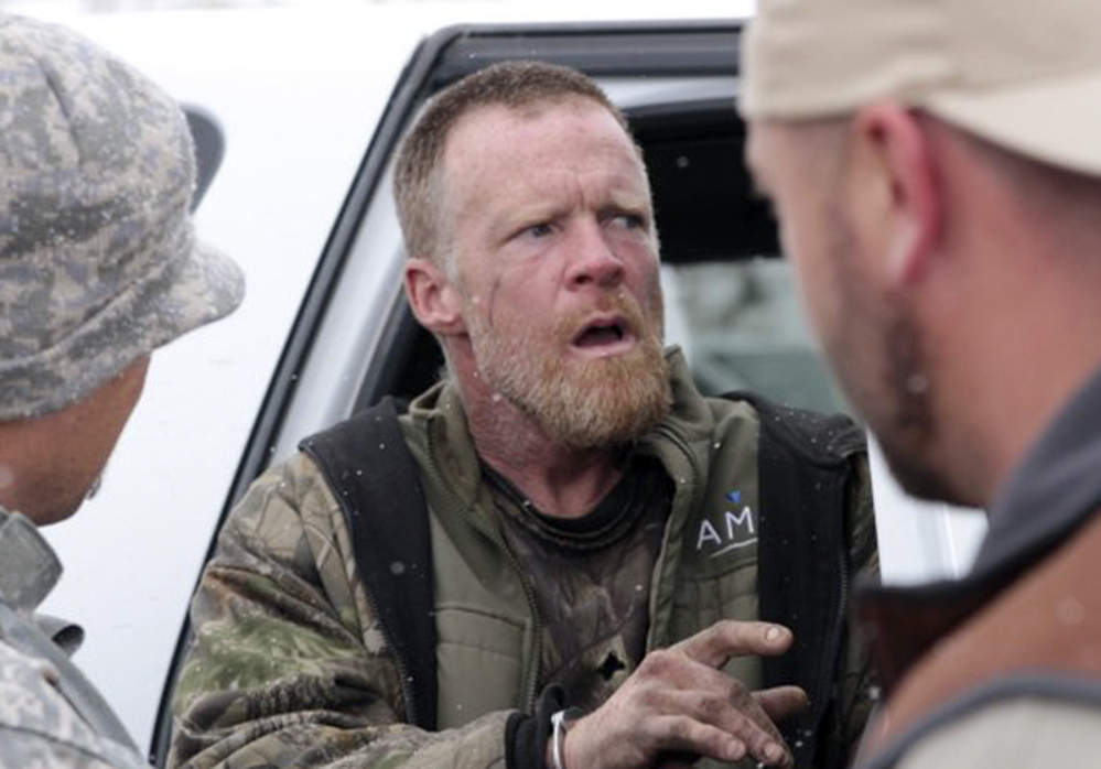 Detectives take fugitive Troy James Knapp into custody in the mountains outside of Ferron in central Utah, in this April 2, 2013, photo, provided by the Emery County Sheriff's Office. The Associated Press