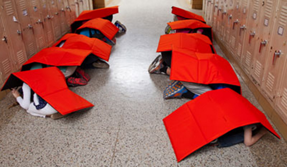 ProTecht photo Children wearing the BodyGuard blanket kneel in a school hallway during a tornado drill.