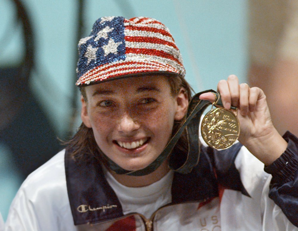 In this July 26, 1996 file photo, Olympic gold medalist Amy Van Dyken holds her medal after winning the women's 50 meter freestyle at the 1996 Summer Olympic Games in Atlanta. Van Dyken has a severed spine after an accident on her all-terrain vehicle in Arizona. A hospital spokeswoman didn't provide details Monday on the injuries. The swimmer was hurt Friday night, June 6, 2014,  and told emergency workers at the scene she could not move her toes or feel anything touching her legs. The Associated Press/Lynne Sladky