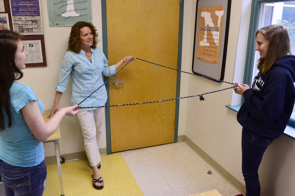 Education technician Deb Downing gets creative during math instruction with Cheyenne Rowe, left, and Emma Gaul in the drop-in learning center at Poland Regional High School. The center is part of the school's student support system. Carl D. Walsh/Staff Photographer