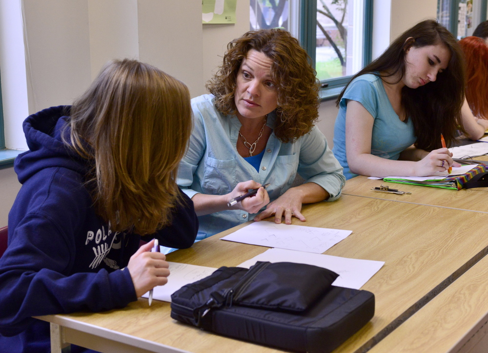 Deb Downing assists Emma Gaul, left, and Cheyenne Rowe with math homework at Poland Regional High School, which has had a proficiency-based program for 13 years. Logan Werlinger/Staff Photographer