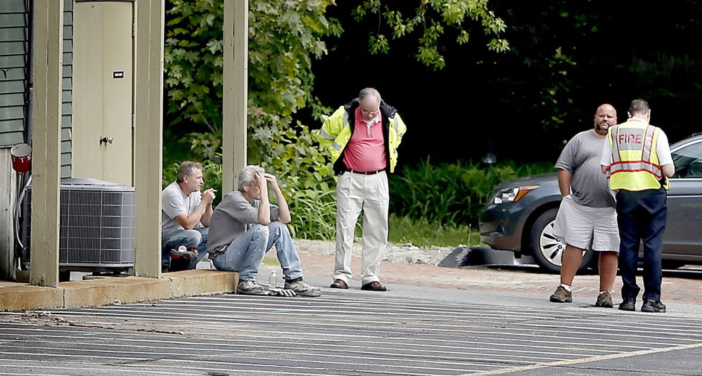 Freeport police and fire crew at the scene of a fatal accident of a landscaping crew member behind 136-140 Main Street in Freeport on Tuesday. A worker for a landscaping crew was killed just before 9 a.m. Authorities would not release the circumstances of the accident but said it appears a piece of equipment may have fallen on the victim. Tim Greenway/Staff Photographer
