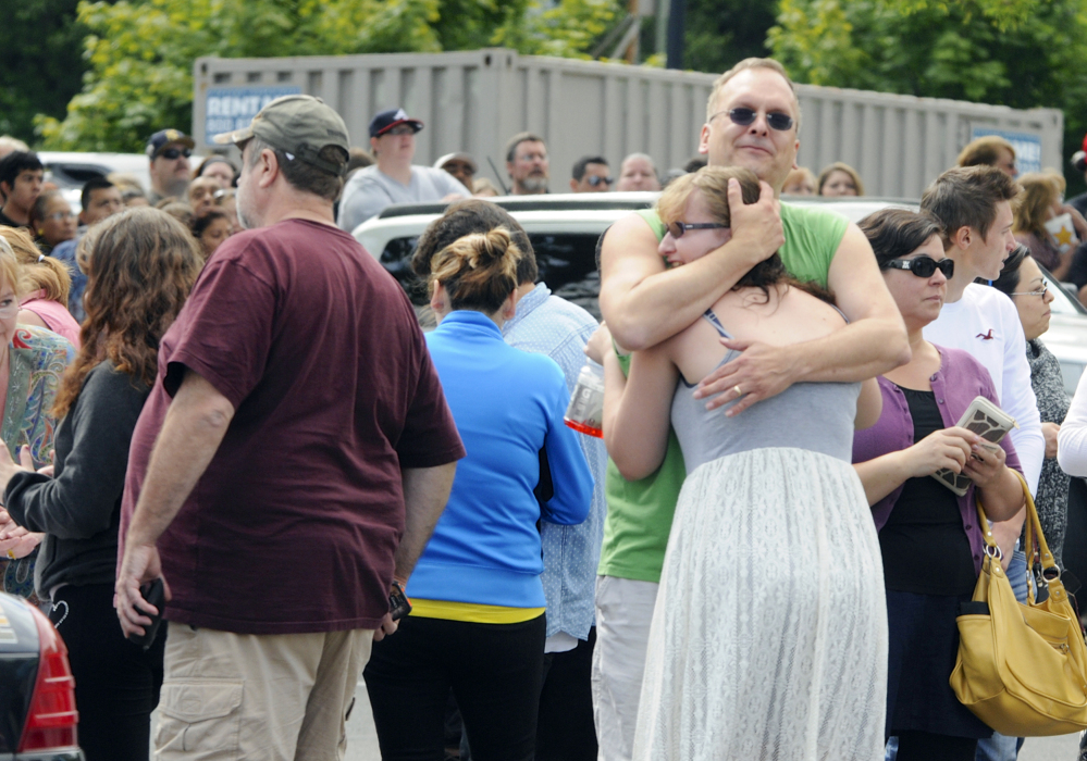 A family embraces as students arrived at the Fred Meyer grocery store parking lot in Wood Village, Ore., after a shooting at Reynolds High School on Tuesday.