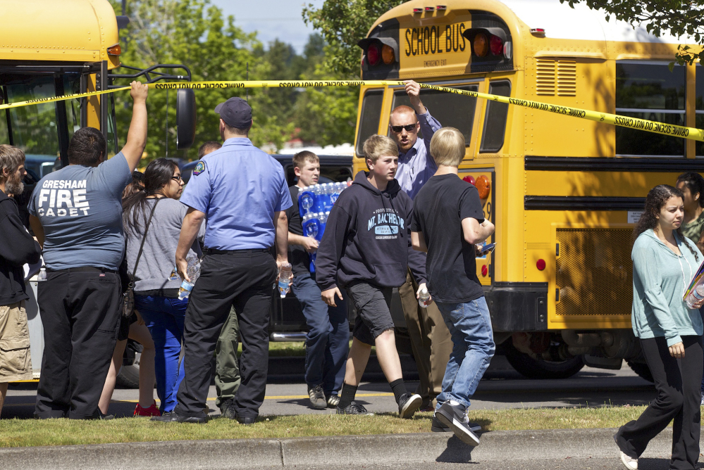 Students arrive by bus at the Fred Meyer grocery store parking lot in Wood Village, Ore., after a shooting at Reynolds High School on Tuesday.