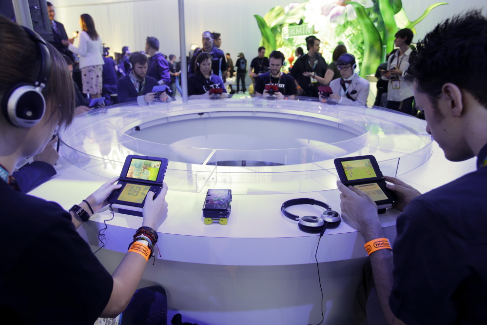 Players try out Nintendo games during an expo in Los Angeles. Nintendo on Tuesday announced that it is introducing a line of toy figures that interact with its games.