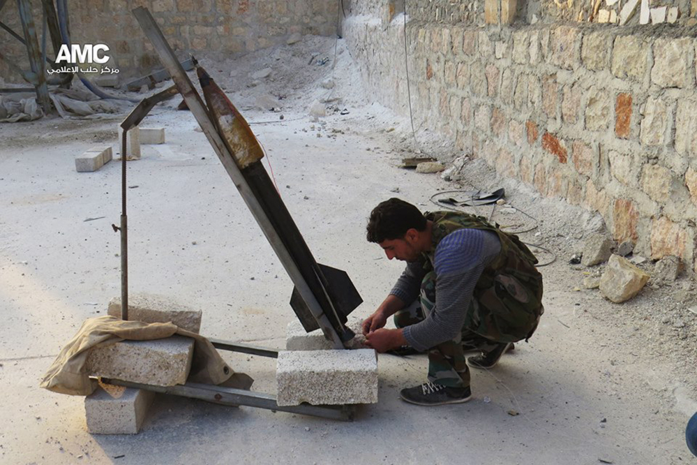 This photo provided by the anti-government activist group Aleppo Media Center (AMC), which has been authenticated based on its contents and other AP reporting, shows a Free Syrian Army fighter as he prepares a locally made missile to be fired against Syrian government forces, in Aleppo, Syria, Tuesday June 10, 2014. This photo provided by the anti-government activist group Aleppo Media Center (AMC), which has been authenticated based on its contents and other AP reporting, shows a locally made shell being fired by the Free Syrian Army towards Syrian government forces, in Aleppo, Syria, Tuesday June 10, 2014. Fighting in eastern Syria between the Islamic rebel brigades and an al-Qaida splinter group has killed more than 630 people and uprooted at least 130,000 since the end of April, an activist group said Tuesday. The Associated Press/Aleppo Media Center