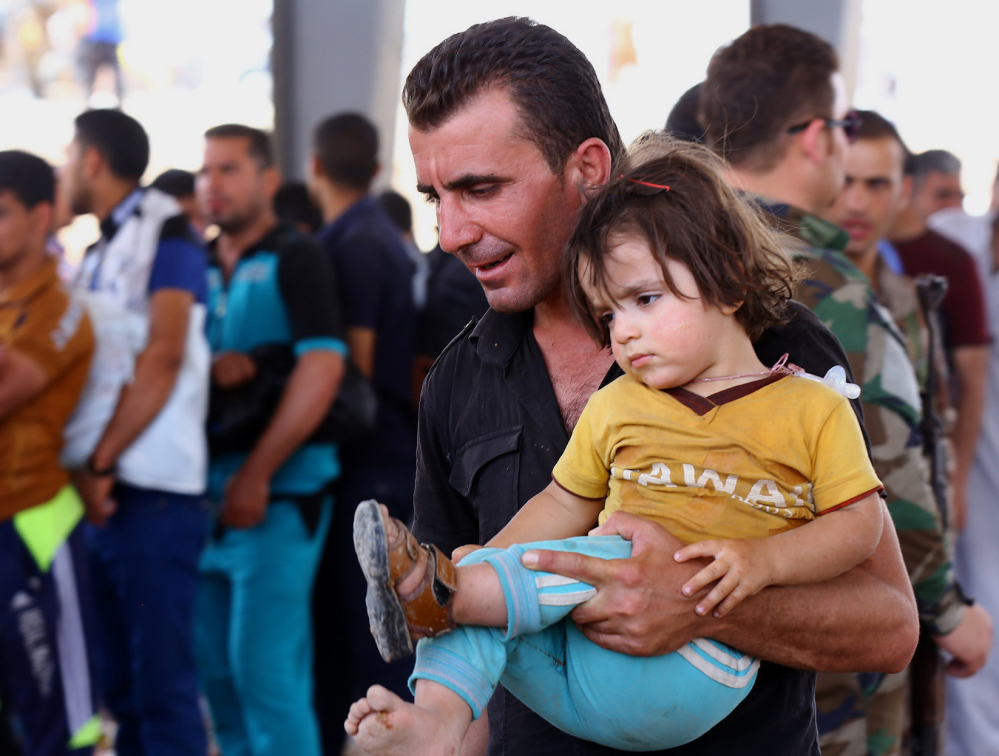 Refugees fleeing from Mosul head to the self-ruled northern Kurdish region in Irbil, Iraq, about 220 miles north of Baghdad on Tuesday. The Associated Press
