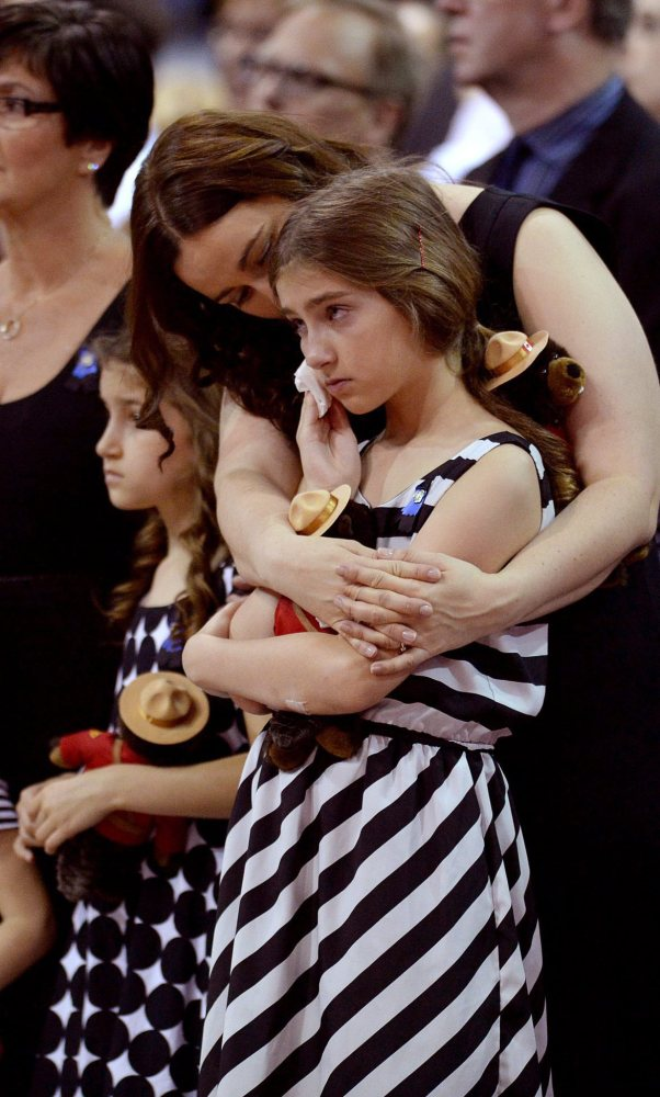 Constable Douglas Larche's family attends Tuesday's services in Moncton, New Brunswick, where three officers were killed last week. The Associated Press