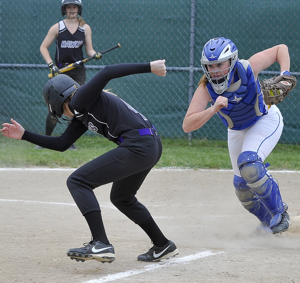Jen Gray of Marshwood attempts to reverse direction and head back to third base Tuesday after seeing Falmouth catcher Jessica Collins hold the ball. Marshwood downed the Yachtsmen 8-3 in a Western Class A prelim. Gordon Chibroski/Staff photographer