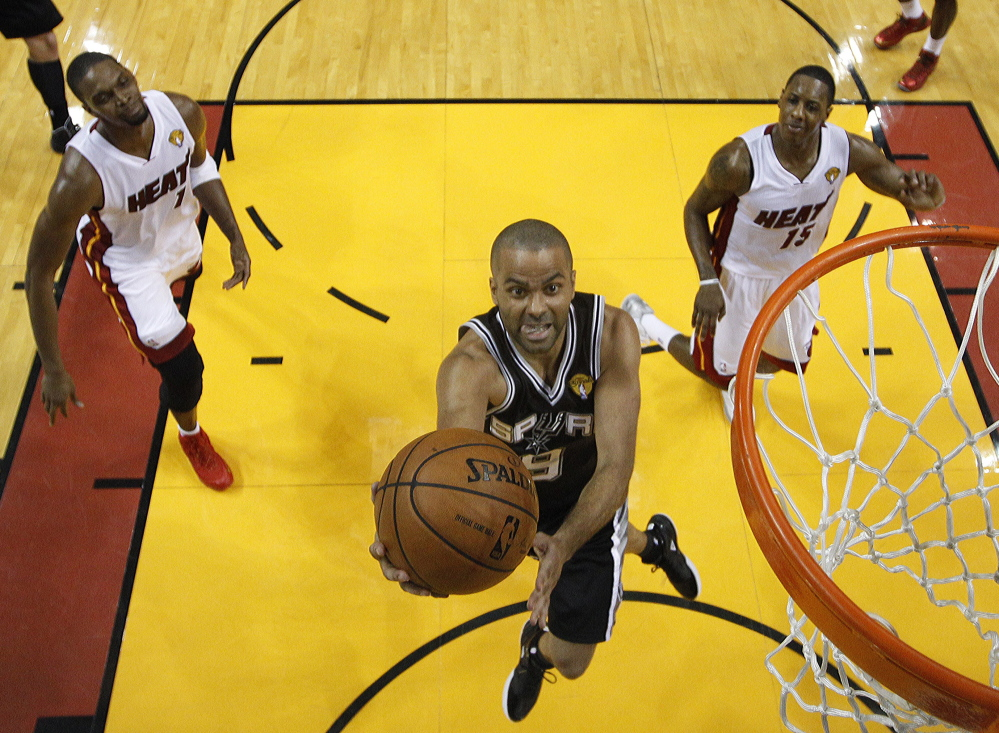 Tony Parker of the San Antonio Spurs finds room to drive Tuesday night between Chris Bosh, left, and Mario Chalmers (15) of the Miami Heat during Game 3 of the NBA finals. San Antonio won, 111-92. The Associated Press