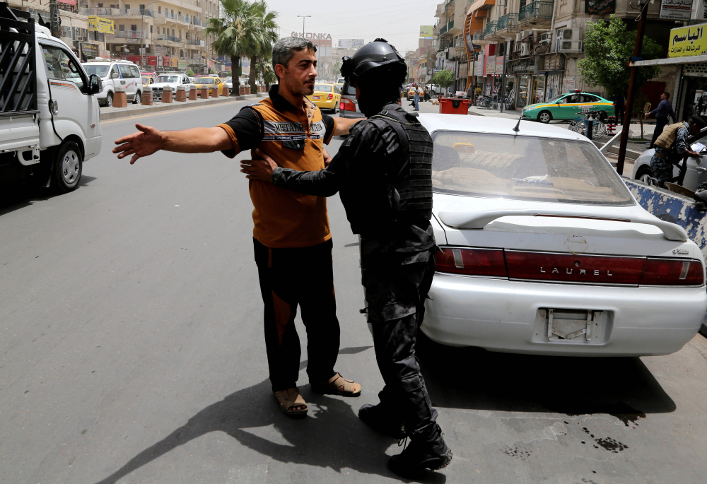 The Associated Press An Iraqi federal policeman searches a man at a checkpoint in Baghdad, Iraq, Wednesday. The Iraqi government has tightened security after a stunning assault in Mosul that exposed Iraq's eroding central authority.