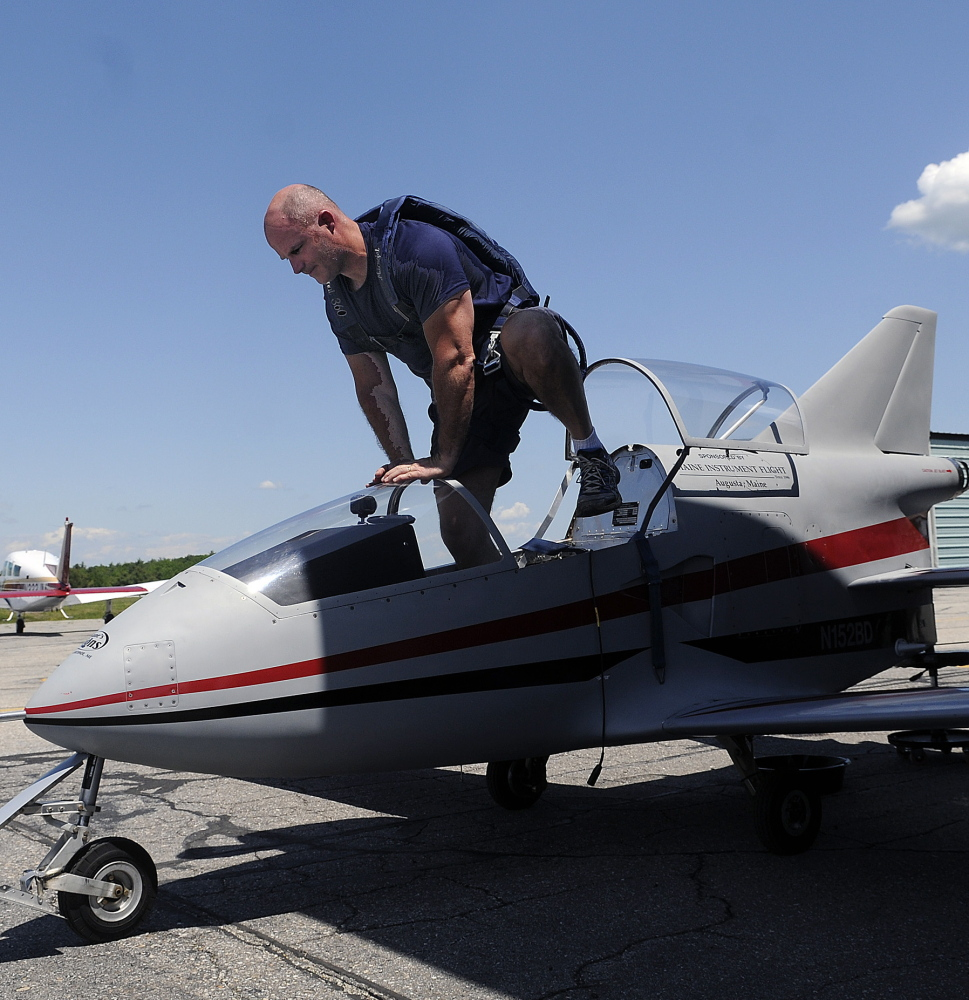 Wearing a parachute, Peter Reny climbs out of his Bede-BD5 microjet after flying around Augusta.