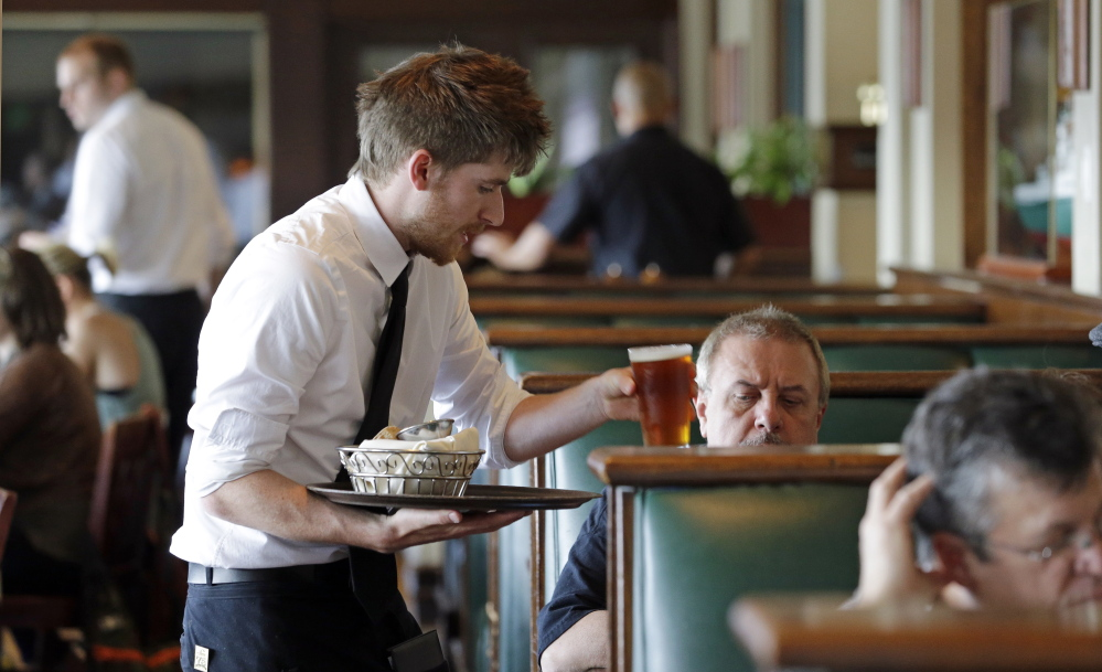 Waiter Spencer Meline serves a customer at Ivar's Acres of Clams restaurant on the Seattle waterfront Wednesday, May 14, 2014. A federal lawsuit filed Wednesday challenges Seattle's adoption of what would be the nation's highest minimum wage as unfair to small franchises.