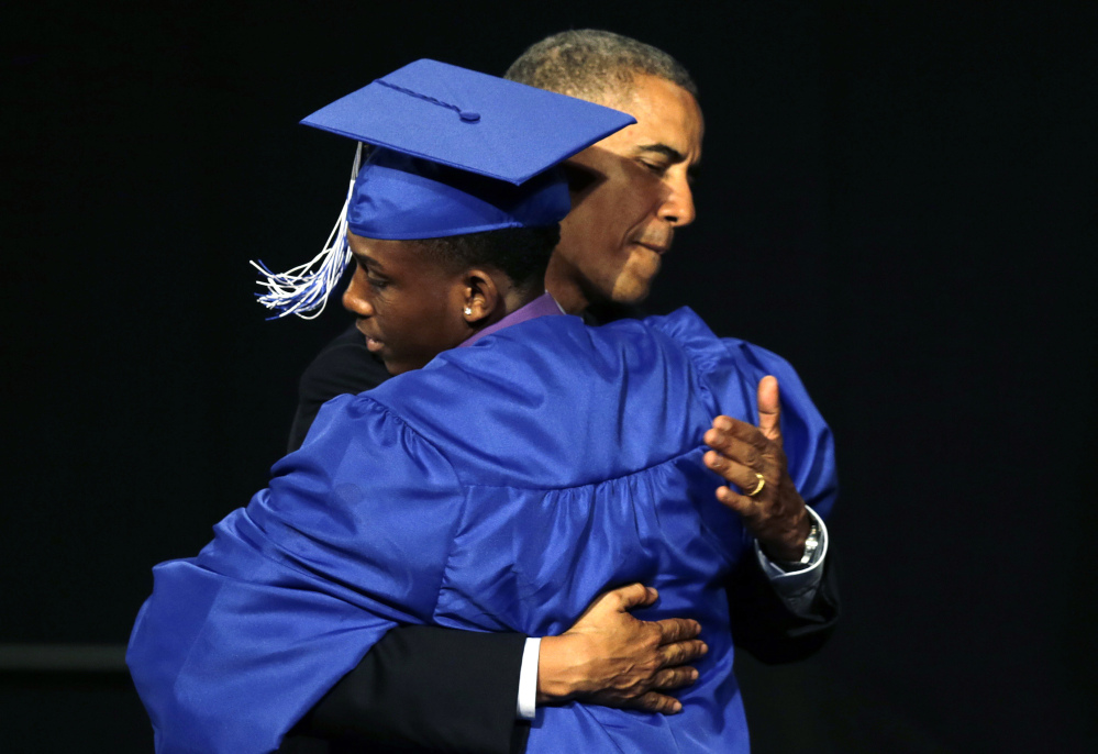 President Barack Obama embraces student Martin Maina during the graduation ceremony for Worcester Technical High School in Worcester, Mass., Wednesday.