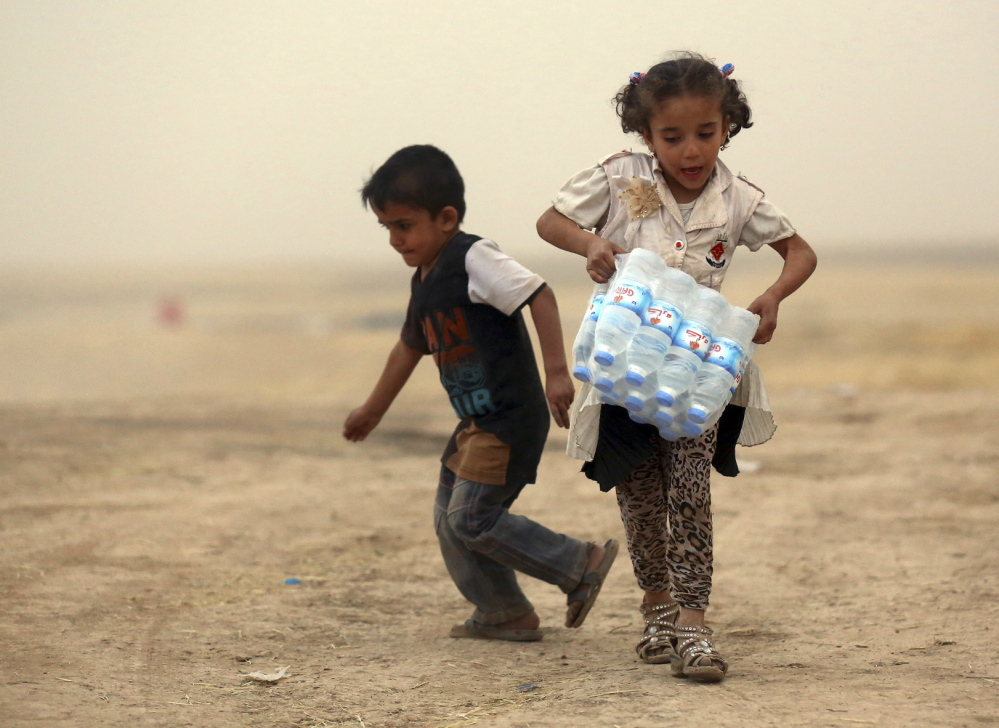 A girl who fled the violence in the Iraqi city of Mosul carries a case of water at a camp on the outskirts of Arbil in Iraq's Kurdistan region on Thursday. Reuters