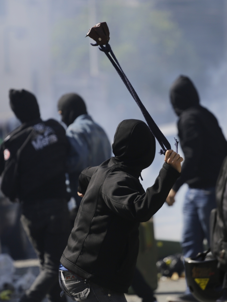 A protester winds up to sling a stone at police after clashes erupted in Sao Paulo on Thursday.