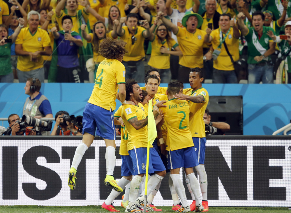 Fans cheer as Brazil players celebrate after scoring on a penalty kick during their group A World Cup soccer match against Croatia in the opening game of the tournament at Itaquerao Stadium in Sao Paulo, Brazil, Thursday, June 12, 2014. Brazil won the match 3-1.